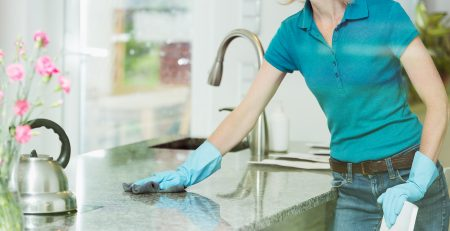 woman wiping down stone kitchen countertop