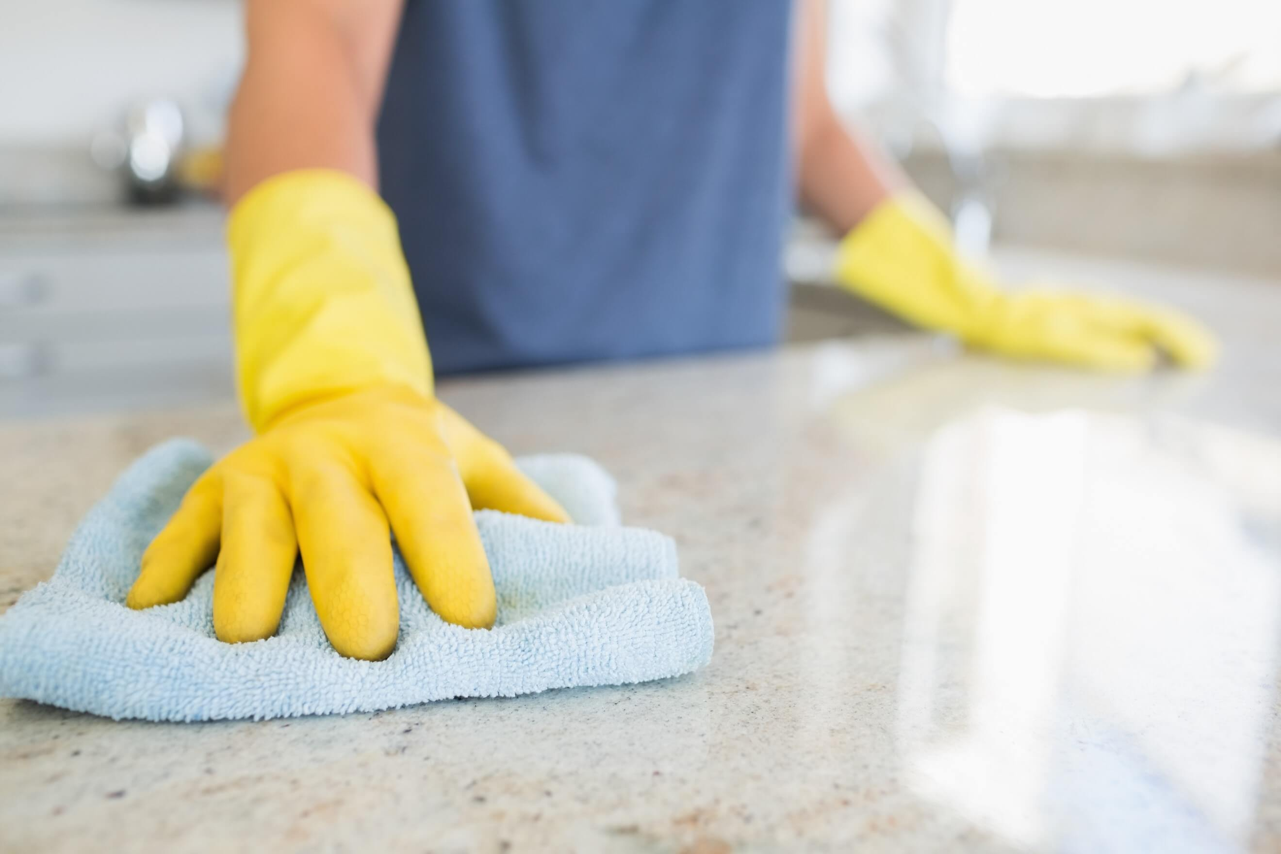 hands in rubber gloves cleaning stone worktop