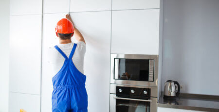 construction man fitting kitchen cupboards