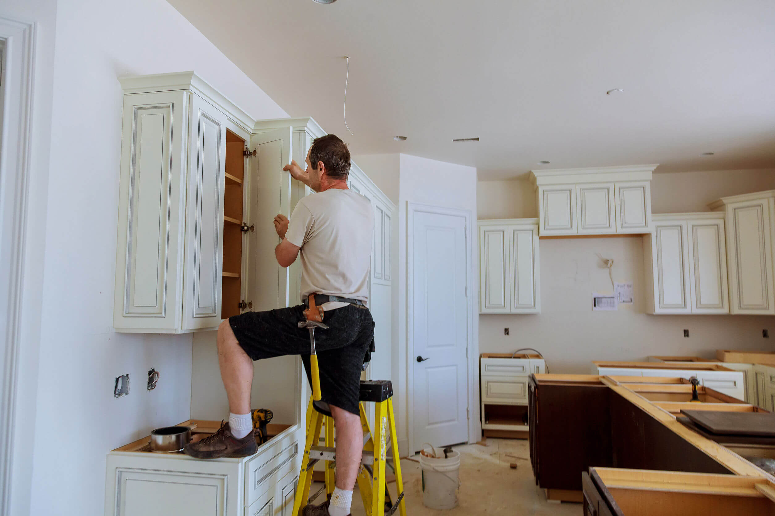 Installation of kitchen. Worker installs doors to kitchen cabinet.