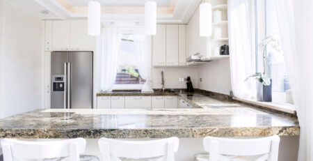 Modern, white kitchen with long granite worktop